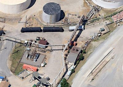 Ariel view of Kinder Morgan Tank Terminals showing long, raised piping runs, silohs, tank style rail cars and sets of pumps on the site with the operations buildong