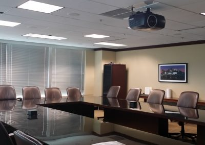 Conference room inside the Norfolk Southern Towers with a large shiny U shaped conference table and brown leather chairs underneath a ceiling mounted projector