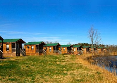 Waterside view of a group of mini log cabins with small front porches at the North Landing RV Park