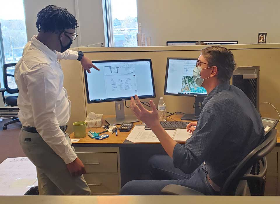 Two design professionals in front of a computer monitor pointing and discussing where plan changes occur